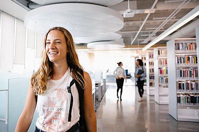 Cheerful student smiling in university library - p1192m2110265 by Hero Images