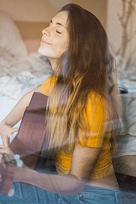 Portrait of content young woman sitting behind windowpane playing guitar - p300m1581521 by Kike Arnaiz