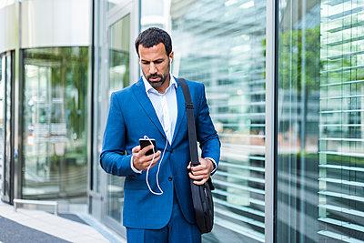 Businessman using smartphone, headphones, laptop bag - p300m1587397 von Daniel Ingold