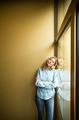 Businesswoman standing on a window, looking on camera, ams crossed - p300m2114756 by Michelle Fraikin