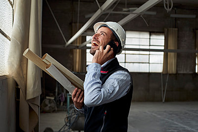 Cheerful male architect laughing while talking over mobile phone in constructing building - p300m2243423 by Veam