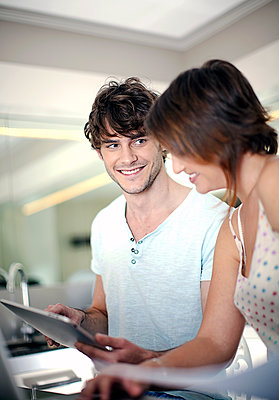 Young man and woman (22-25) looking at iPad and paperwork in the kitchen, Cape Town, South Africa - p300m2293235 von LOUIS CHRISTIAN
