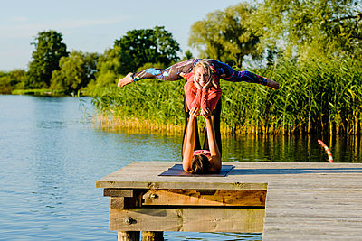 Portrait smiling women practicing acro yoga on sunny lakeside dock - p301m2075550 by Sven Hagolani