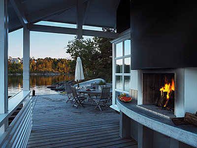 A fireplace in a veranda by the water. - p31215549f by Mikael Dubois