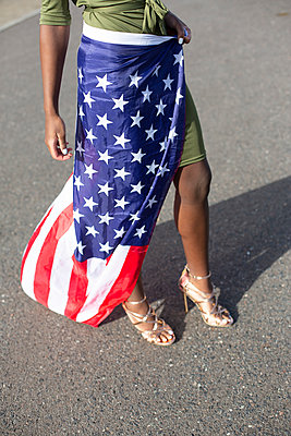Woman with black ethnicity wrapped in American flag - p975m2247760 by Hayden Verry
