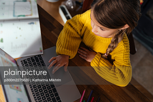 Girl in yellow sweater e-learning through laptop at home - p300m2275620 by Katharina Mikhrin