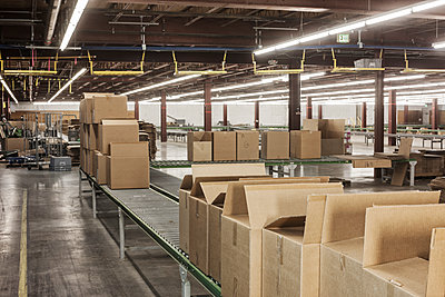 Interior view of a large distribution warehouse showing a motorized conveyor system to move products stored in cardboard boxes. - p1100m1575467 by Mint Images