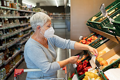 Caucasian elderly woman with white hair  shopping in supermarket - p1166m2208392 by Cavan Images