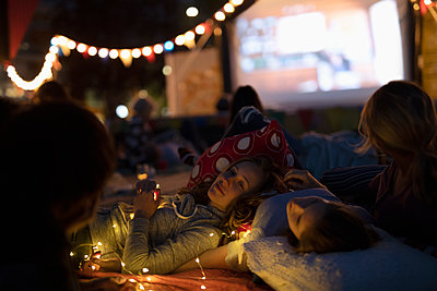 Teenage girls relaxing, enjoying movie in the park - p1192m2024248 by Hero Images