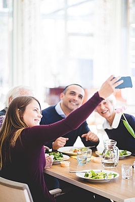 Young woman taking selfie with father and grandparents while having lunch in nursing home - p426m2018566 by Maskot