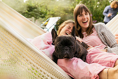 Two women with dog in hammock - p788m2031166 by Lisa Krechting