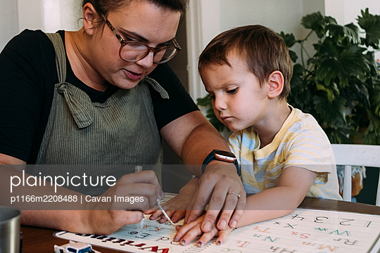 Mom painting her young son's finger nails at dining table - p1166m2208488 by Cavan Images