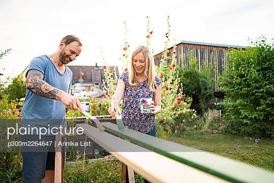 Happy couple painting wooden plank in garden - p300m2264647 by Annika List