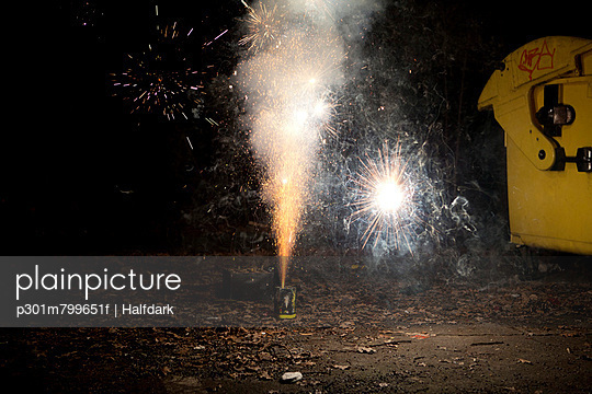 Sparks and smoke coming out of a firework exploding on a sidewalk - p301m799651f by Halfdark