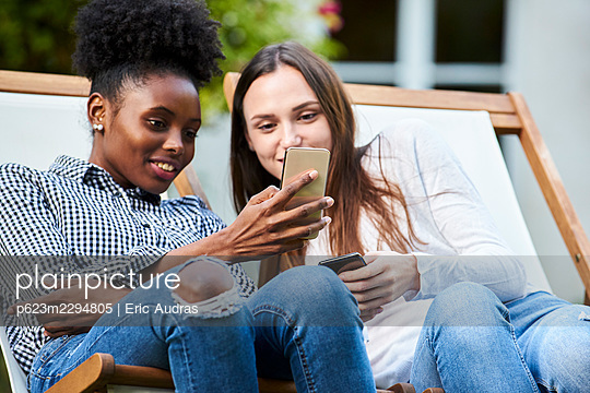 Smiling young friends using smartphones in park - p623m2294805 by Eric Audras