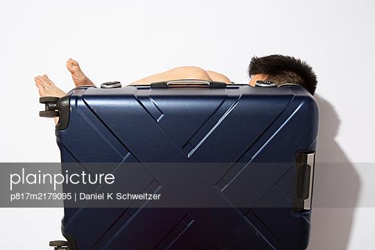 Naked man hiding behind trolleybag - p817m2179095 by Daniel K Schweitzer