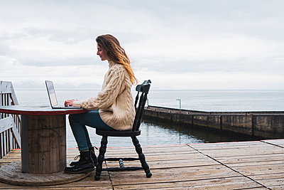 Iceland, woman using laptop at the sea - p300m2004010 by Kike Arnaiz