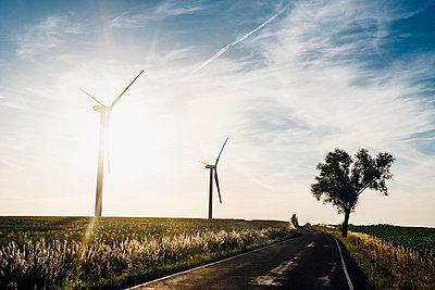 Empty country road and wind turbines at sunset - p300m2005488 von Jana Mänz