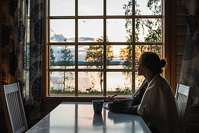Finland, Lapland, young woman sitting at the window looking at a lake - p300m2060849 von Kike Arnaiz
