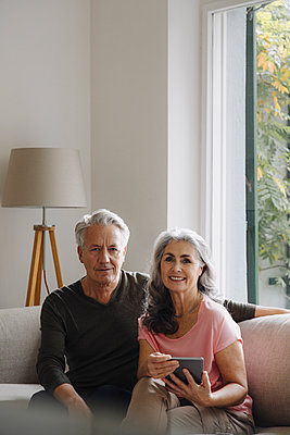Portrait of senior couple relaxing on couch at home - p300m2156254 by Gustafsson