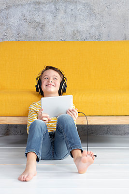 7 year old boy playing with tablet and wearing headphones on yellow couch in front of concrete wall - p300m2170307 von Epiximages