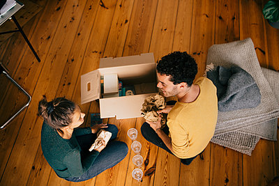 High angle view of couple removing glasses from box in living room at new home - p426m2138272 by Maskot