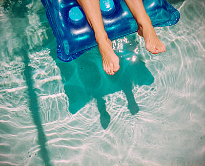 Feet of Caucasian woman floating on raft in swimming pool - p555m1409547 by Shestock