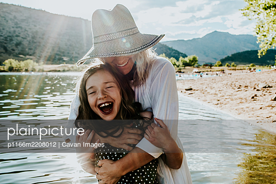 Mom and daughter hugging and laughing while standing in a lake - p1166m2208012 by Cavan Images