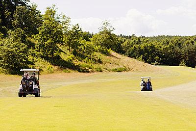 Golf carts on field by trees - p1264m1173246 by Lisa Lindqvist Liljedahl