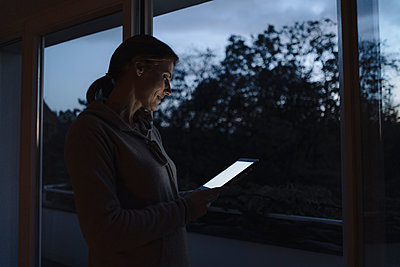 Woman using digital tablet, standing at window in twilight - p300m2155370 by Joseffson