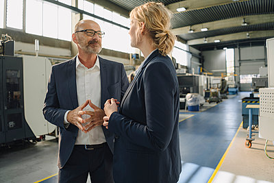 Businessman and businesswoman talking in a factory - p300m2170449 by Kniel Synnatzschke