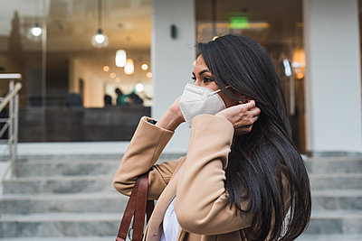 Woman wearing protective face mask standing by steps outside building during COVID-19 - p300m2242494 by MORNINGVIEW AGENCY