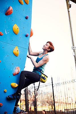 Caucasian woman climbing outdoor climbing wall - p555m1305450 by Granger Wootz