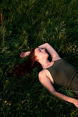 Young woman lying on the meadow - p947m2273200 by Cristopher Civitillo