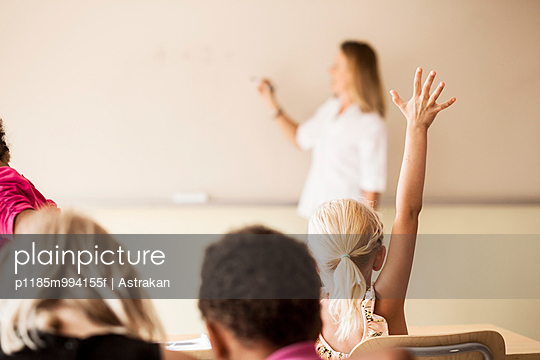 Mature teacher teaching mathematics to children in classroom