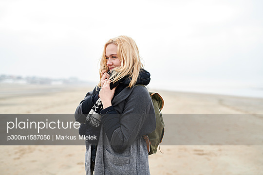 Portrait of blond young woman with backpack on the beach in winter - p300m1587050 von Markus Mielek