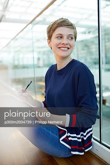 Blond businesswoman sitting on ground, writing in notebook - p300m2004739 von Philipp Nemenz