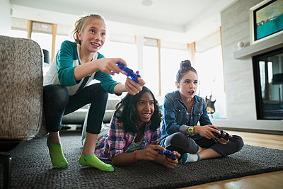 Girls playing video game living room rug - p1192m1129541f by Hero Images