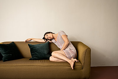 Brunette woman chills on sofa - p294m2132903 by Paolo