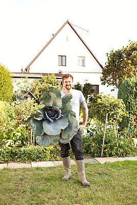 Portrait of man standing in the garden presenting red cabbage - p300m1188802 by Michelle Fraikin