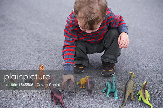 High angle view of boy playing with dinosaur figurines while crouching on road - p1166m1545506 by Cavan Social