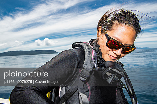 woman getting ready for a dive in Raja Ampat / Indonesia - p1166m2279275 by Cavan Images