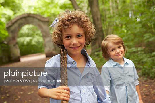 Portrait of boy with wood stick and friend in forest - p300m2180039 by Stefanie Aumiller