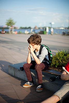 Nachdenklicher Junge sitzt auf seinem Longboard - p1195m1138166 von Kathrin Brunnhofer
