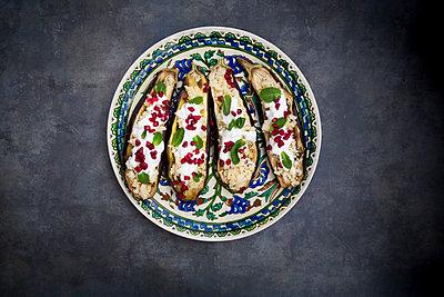 Filled aubergine, couscous, yogurt sauce, mint and pomegranate seeds - p300m1549420 by Larissa Veronesi