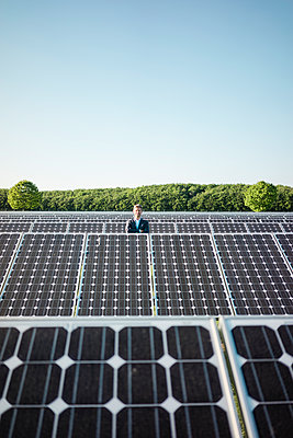 Mature man standing on panel in solar plant - p300m2004777 by Robijn Page