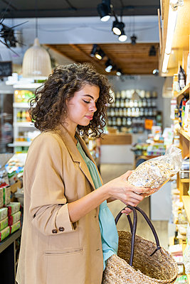 Young woman shopping in a food shop - p300m2118538 by VITTA GALLERY