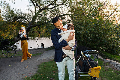 Father carrying baby - p312m2237435 by Pernille Tofte