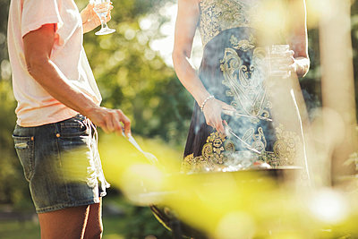 Midsection of women cooking on barbecue grill at back yard - p426m1226270 by Maskot