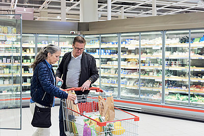 Man looking while woman keeping bottle in shopping cart at supermarket - p426m1451855 by Maskot